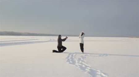 öneri : Guy gets on one knee and doing the girl a marriage proposal  in the middle of a snow field