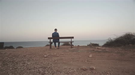 одиноко : Young man sitting on a bench and looking at the empty seat beside, sea on the background