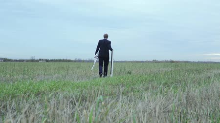 artistas : Slow motion shot of a man in a suit with his easel and canvas walking in the green grass of a field Vídeos