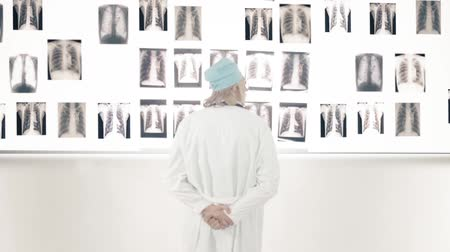 рентгенологическое : Dolly shot of a male doctor looking at x-ray images on the wall