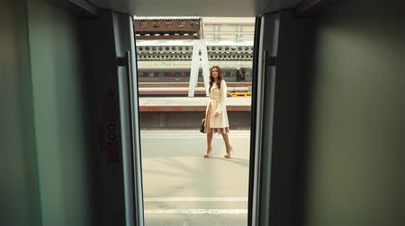 platforma : View from the wagon of the train on young woman on the station platform waiting for someone