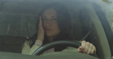 pŁacz : Portrait through the windshield of unhappy, crying girl driving a car
