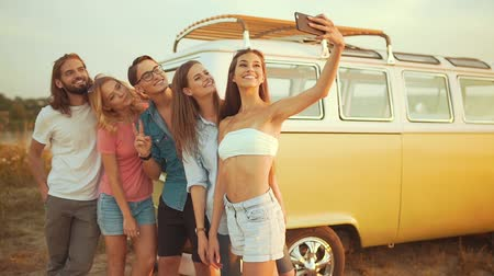dospělý : Friends Taking Photo On Phone In Nature In Summer. Happy Young Men And Beautiful Women Enjoying Summer Travel On Vacation, Spending Leisure Time Together Near Retro Bus Outdoors. Dostupné videozáznamy