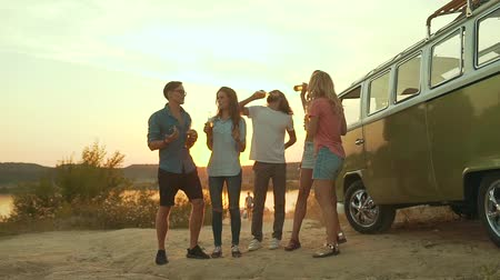 Деятельность выходные : Young Friends Dancing And Drinking In Nature. Beautiful Happy People With Drinks Having Fun On Weekend In Summer. Friends Enjoying Outdoor Party Near Retro Bus.