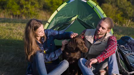 sátor : Man And Woman Traveling With Dog At Camp, Sitting Near Camping Tent And Playing With Pet On Nature.