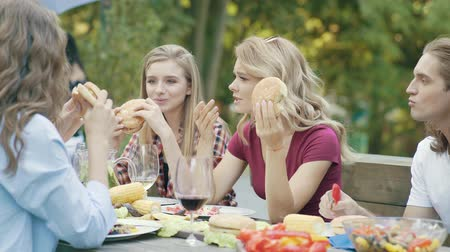 barbekü : Happy Young Friends Eating Burgers Sitting At Dinner Table At Barbecue Outdoor Party