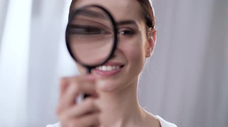 pertavsız : Woman Looking Through Magnifier And Smiling Close Up