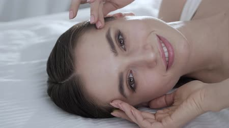 naturalmente : Face Care. Young Woman Lying On Bed And Touching Skin On Face Vídeos