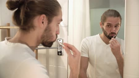 escova de dentes : Man Brushing Teeth And Looking At Mirror In Bathroom