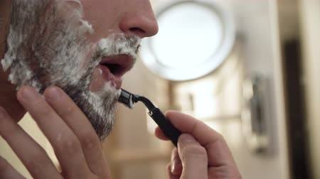 shaving foam : Men Face Hair Care. Male Shaving Beard With Razor Closeup Stock Footage