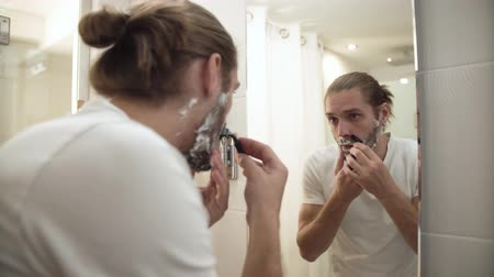 shaving foam : Man Shaving Beard With Razor In Bathroom Stock Footage