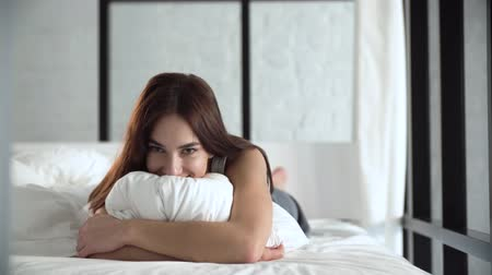 kaukázusi : Beautiful Woman Lying On Comfortable Bed And Hugging Pillow Stock mozgókép