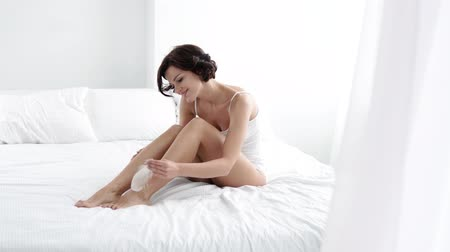 dokunaklı : Skin Care. Woman Touching Leg With Feather Sitting On Bed