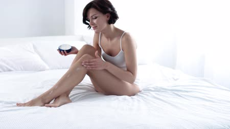 sensível : Body Skin Care. Woman Applying Body Cream On Leg Skin At Bedroom