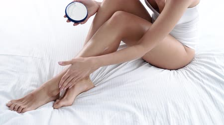 underwear : Body Skin Care. Woman Applying Body Cream On Leg Skin At Bedroom