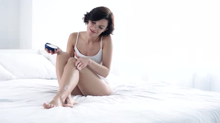 postel : Body Skin Care. Woman Applying Body Cream On Leg Skin At Bedroom