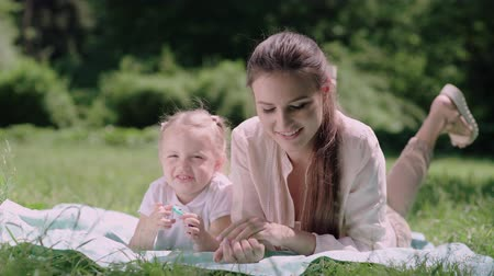 kids : Mom And Child Lying And Resting On Blanket At Park Stock Footage