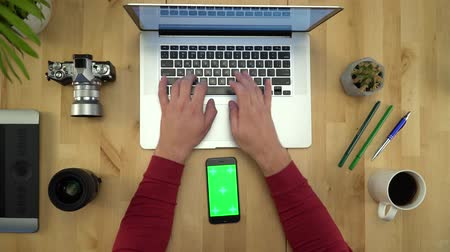 netbook : Flat Lay Of Man Hands Using Phone With Green Screen At Workplace