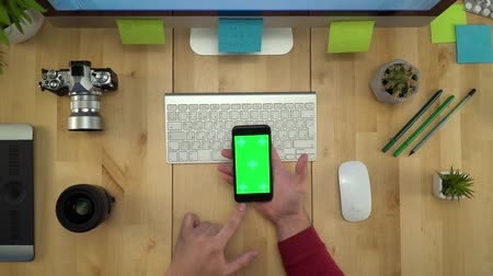 gadżet : Flat Lay Of Man Hands Using Phone With Green Screen At Workplace