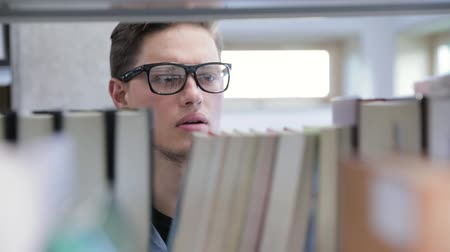 educado : College Library. Male Student Searching For Book On Bookshelves Vídeos