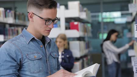 művelt : Student At Library Reading Books Near Bookshelves