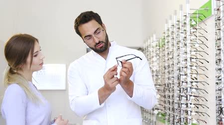 optyk : Optical Store. Eye Doctor Helping Woman Choosing Eyeglasses Wideo