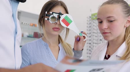 тестирование : Eye Exam. Doctors Checking Woman Eyesight With Optometry Glasses Стоковые видеозаписи