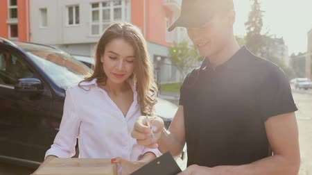 postacı : Delivery Service. Woman Receiving Package From Courier, Signing Delivering Document Outdoors Stok Video
