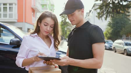 navlun : Delivery Service. Woman Receiving Package From Courier, Signing Delivering Document Outdoors Stok Video
