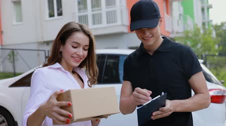 listonosz : Delivery. Express Courier Delivering Package To Client, Woman Signing Delivery Documents Outdoors Wideo