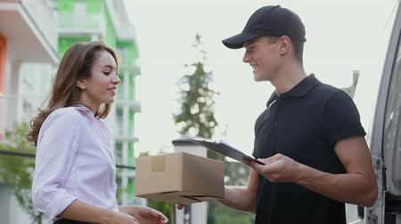 postacı : Delivery Courier Service. Man Delivering Package To Woman, Client Signing Delivery Document Near Van Stok Video