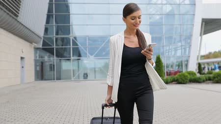 手荷物 : Business Trip. Beautiful Woman With Phone And Suitcase Walking Near Airport Outdoors