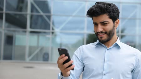 desgaste : Handsome Man Using Phone Near Business Center On Street. Smiling Business Man With Phone Near Office Outdoors Stock Footage