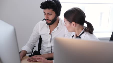 dispatcher : Call center. Operators Working In Contact Center. Man And Woman In Headsets Working Together At Computer