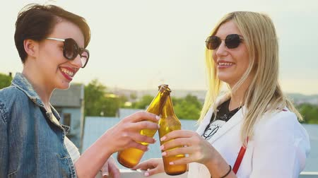 общаться : Young Women Drinking Beer Outdoors, Having Fun Outdoors. Smiling Girls With Bottles In Hands Стоковые видеозаписи
