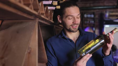 изделия из дерева : Handsome Man Holding Bottle Of Wine In Cellar Winery