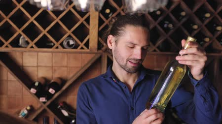 zvyk : Handsome Man Holding Bottle Of Wine In Cellar Winery