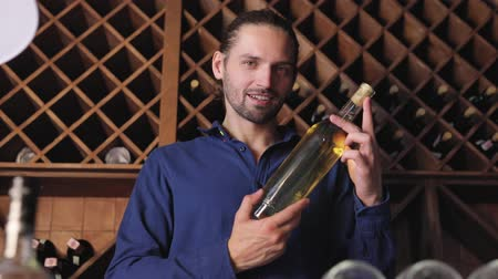aperitief : Handsome Man Holding Bottle Of Wine In Cellar Winery