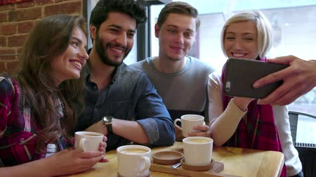 Happy Friends Making Video Call With Mobile Phone In Cafe Wideo