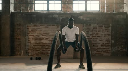 cordas : Fitness workout. Sport man doing battle rope exercise at gym. Black male athlete exercising, doing functional fitness training with heavy ropes indoors
