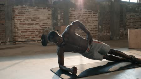 Sport man doing plank exercise, fitness workout at gym. Black male athlete with fit body exercising on yoga mat, planking indoors