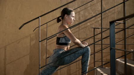 Fitness woman stretching legs on stairs before workout. Beautiful girl athlete with fit body in sport clothes warming up, doing leg stretch, lunge exercise before training or running