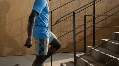 Fit man stretching legs, doing lunge exercise on stairs before workout. Black male athlete in sport wear warming up, doing leg stretch before training or running