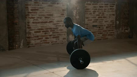 Sport man using chalk powder on hands and lifting weights at gym. Black male athlete applying talc or magnesium powder on hand and lifting barbell, doing deadlift exercise at fitness club Wideo