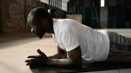 Workout. Black sport man doing plank exercise for tights at gym. Male athlete exercising on yoga mat, planking and moving legs aside indoors Wideo