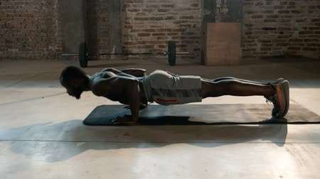 Exercise Sport man working out in gym, doing push-up. Strong muscular athletic black male with fit body exercising, doing push-ups training indoors
