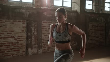 Workout. Woman doing high knees running in place, cardio exercise at fitness gym.Young athletic girl with fit body running on spot, having high intensity fat burning training at sport club indoors