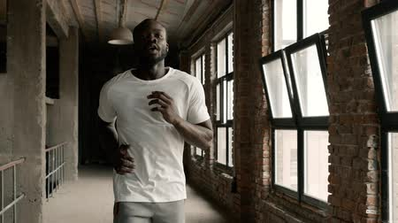 Fit black man in sport wear running near windows indoors. Portrait of athletic male sportsman with fit body jogging at gym