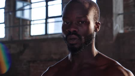 Portrait of black sport man after functional workout at gym. Closeup of handsome tired african male athlete with topless fit body looking at camera, resting after functional training indoors