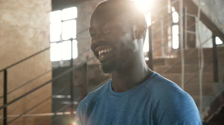 Portrait of happy black man smiling at camera indoors on sunny day. Young african american male athlete with smile on face in blue t-shirt standing near stairs